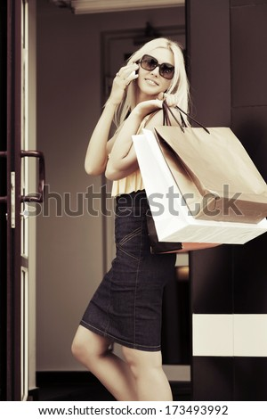 Happy blond woman with shopping bags calling on the phone - stock photo