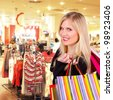 Happy blond woman with shopping bags in shopping center - stock photo