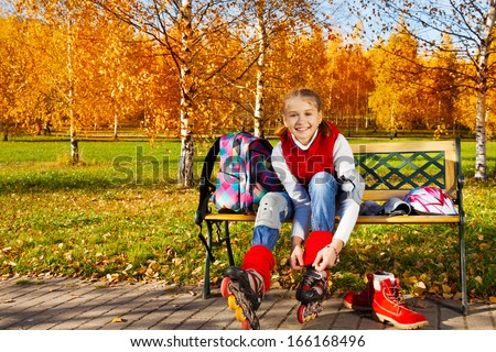 Happy blond 11 years old girl with amazing smile tie shoelaces on roller blades to go skating sitting on the bench in the autumn park on sunny day and turning face to camera, front view - stock photo