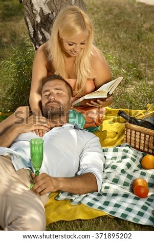 Happy blonde casual attractive woman reading for resting, handsome man after picnic. Smiling, high angle, outdoor. - stock photo