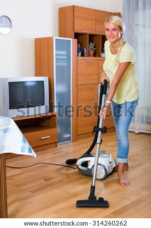 Happy blonde girl hoovering in living room and smiling - stock photo