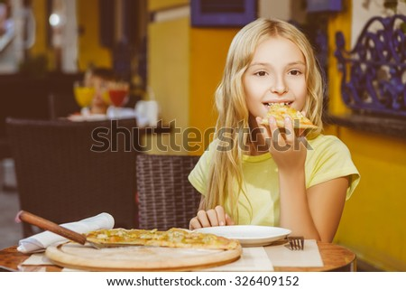 Happy blonde girl indoors eating pizza smiling - stock photo