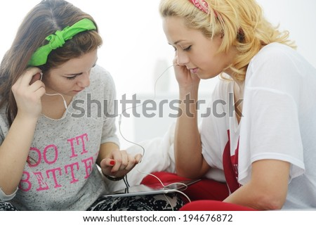 Happy blonde girl on bed in bedroom using tablet for listening music - stock photo