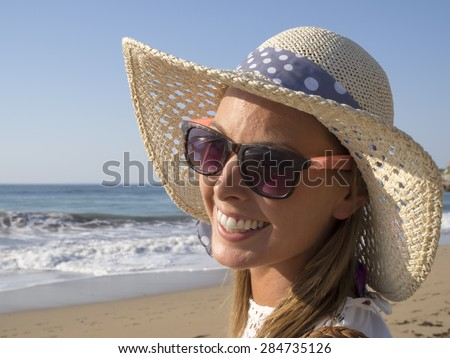 happy blonde girl smiling portrait in the beach  wearing hat and sunglasses, summer holidays - stock photo