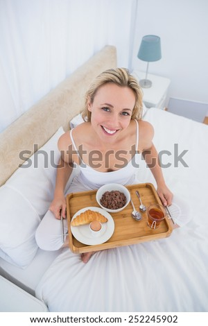 Happy blonde having breakfast in bed at hone in the bedroom - stock photo