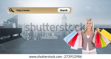 Happy blonde holding shopping bags against large city on the horizon - stock photo