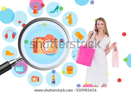 Happy blonde holding shopping bags and talking on phone against dot pattern - stock photo