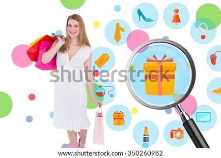 Happy blonde holding shopping bags in white dress against dot pattern - stock photo