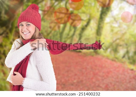 Happy blonde in winter clothes against peaceful autumn scene in forest