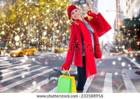 Happy blonde in winter clothes holding shopping bags against blurry new york street - stock photo