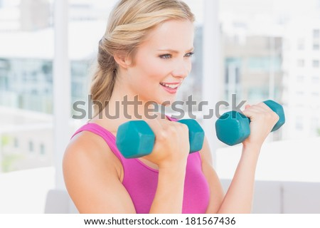 Happy blonde lifting dumbbells at home in the living room - stock photo