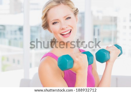 Happy blonde lifting dumbbells smiling at camera at home in the living room - stock photo