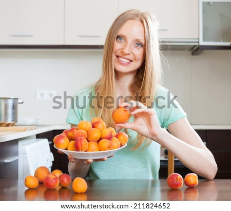 Happy blonde long-haired girl holding apricots in home kitchen