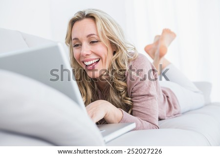 Happy blonde lying on couch using laptop at home in the living room - stock photo