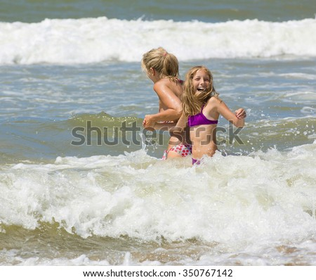 Happy blonde mother and daughter play among waves of sea