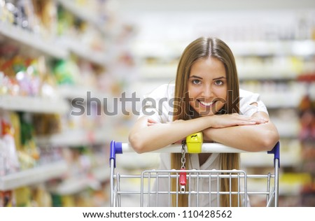Happy blonde shopper smiles over supermarket shopping cart - stock photo