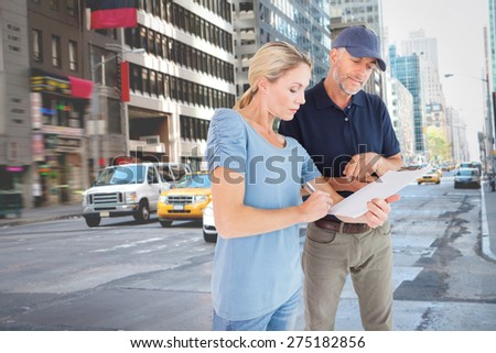 Happy blonde signing for a delivery against new york street - stock photo