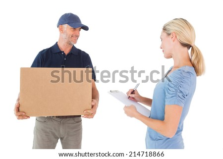 Happy blonde signing for a delivery on white background - stock photo
