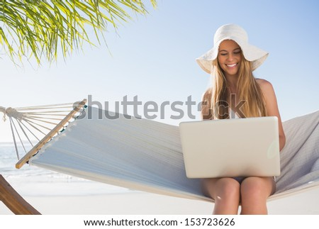 Happy blonde sitting on hammock using laptop at the beach - stock photo
