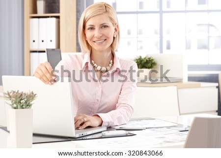 Happy blonde, smiling, casual caucasian female receptionist with laptop computer at business office. Close up, looking at camera.