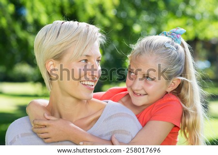 Happy blonde with her daughter in the park on a sunny day