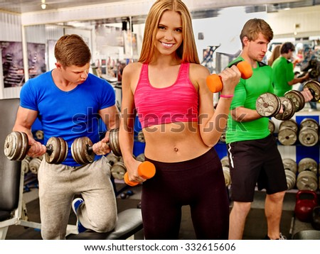 Happy blonde woman and two men concentrated work with dumbbells in the gym. - stock photo