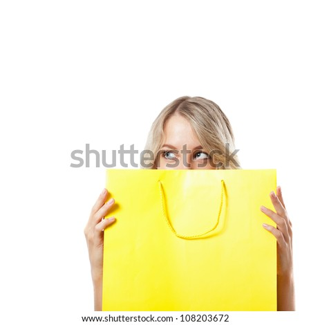 happy blonde woman behind yellow shopping bag - stock photo
