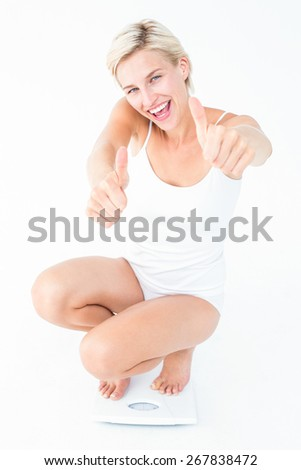 Happy blonde woman crouching on a scales with thumbs up on white background - stock photo
