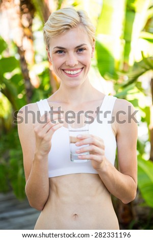 Happy blonde woman holding pill and glass of water outside on a sunny day - stock photo