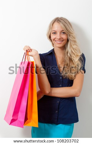 happy blonde woman holding shopping bags near white wall - stock photo