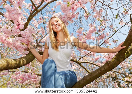 Happy blonde woman in spring sitting in a blooming cherry tree