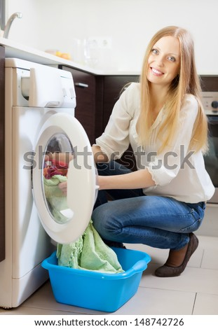 Happy blonde woman loading clothes into the washing machine  at home