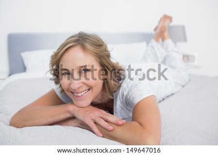 Happy blonde woman lying on bed smiling at camera in bedroom at home - stock photo