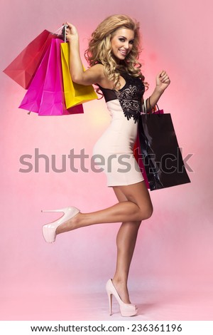 Happy blonde woman posing with bags, shopping. Girl smiling , looking at camera. - stock photo