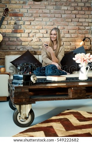 Happy blonde woman resting at home on sofa, using mobilephone, smiling.