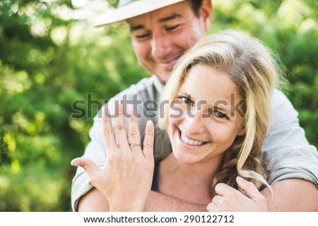 Happy blonde woman showing engagement ring - stock photo