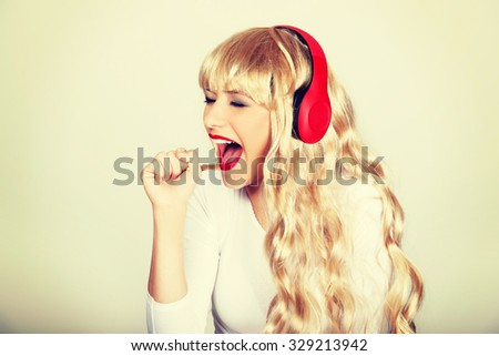 Happy blonde woman singing and listening to the music. - stock photo