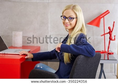 Happy blonde woman sitting at desk, using laptop computer, smiling at camera. - stock photo