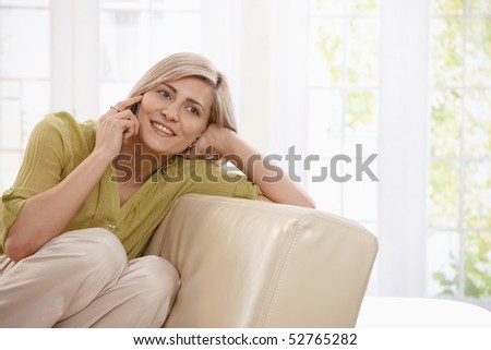 Happy blonde woman sitting on sofa at home, calling with mobile phone smiling. - stock photo