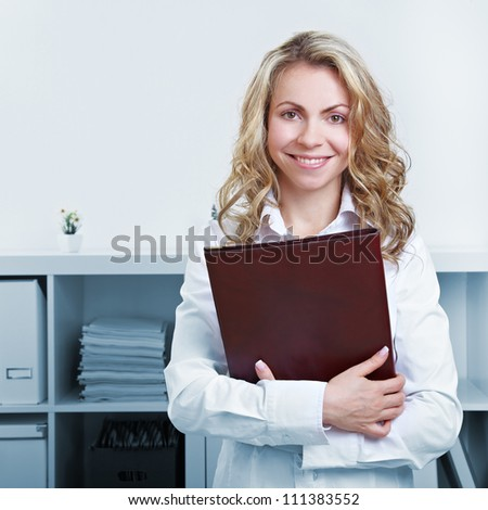 Happy blonde woman with CV and resume in the office - stock photo