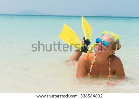 Happy blonde woman with flipper and snorkel mask lying on front in turquoise water of the tropical beach.Copy space - stock photo