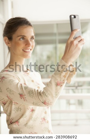Happy blonde young woman with mobile phone - stock photo