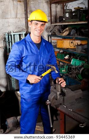 happy blue collar worker working in workshop - stock photo