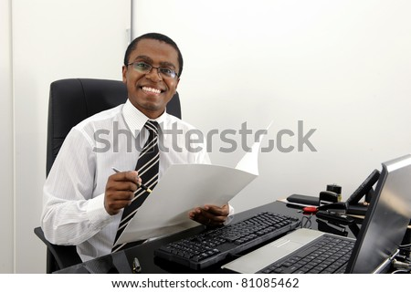 Happy bookkeeper reading documents at desk - stock photo