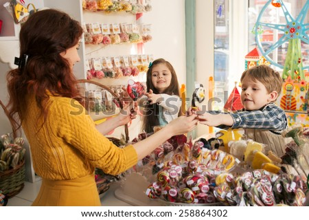 Happy boy and girl buying sweets in the store. Beautiful woman salesman gives candies to children  - stock photo