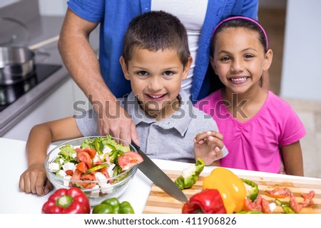 Happy boy and girl chopping vegetables in the kitchen - stock photo