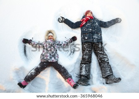 Happy boy and girl  having fun together laying in a snow making snow angels