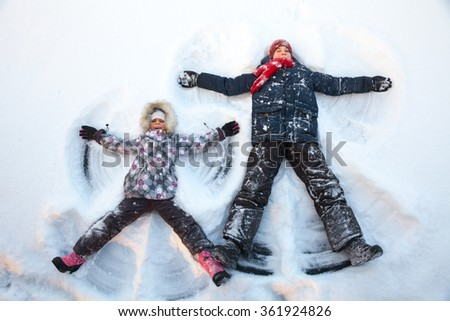 Happy boy and girl  having fun together lying in a snow making snow angels - stock photo