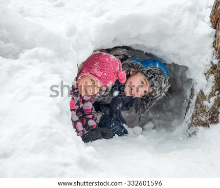 Happy boy and girl looking out from a snow cave they made in a snowdrift - stock photo