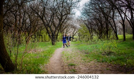 happy boy and girl running in the spring garden